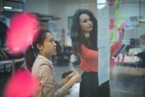 Жіночий керівників, обговорюючи над наліпок в офісі — стокове фото