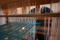 Розділ середині старший жінка, ткацтва з шовку в магазин — стокове фото
