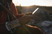 Maasai man in traditional clothing using mobile phone at countryside — Stock Photo