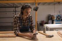 Молодая женщина ремесленница с помощью мобильного телефона в мастерской . — стоковое фото