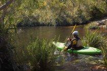 Жінка каяках в річці рослинність. — стокове фото