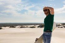 Hombre con pie de sandboard en el desierto en un día soleado - foto de stock