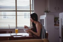 Woman having breakfast on dinning table at home — Stock Photo