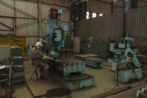 Trabalhador, usando a máquina de trituração na oficina — Fotografia de Stock