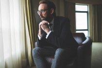 Homme d'affaires pensif assis sur la chaise de bras dans la chambre d'hôtel — Photo de stock