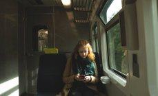 Junge Frau benutzt Handy während Zugfahrt — Stockfoto