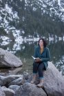 Thoughtful woman sitting with book at lakeside during winter — Stock Photo