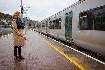 Young woman standing on platform in front of train on a rainy day — Stock Photo