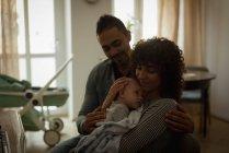 Родители держат ребенка в гостиной дома — стоковое фото