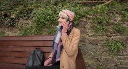 Giovane donna che parla al telefono mentre siede sulla panchina al parco — Foto stock