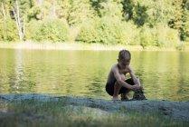 Хлопчик грає з піском поблизу riverbank на сонячний день — стокове фото