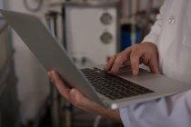 Sección media del trabajador que utiliza el ordenador portátil en la fábrica de ginebra - foto de stock