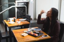 Young woman having sushi food in restaurant — Stock Photo