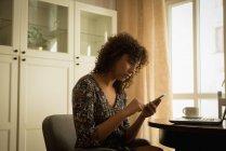 Жінка на дому за допомогою мобільного телефону — стокове фото