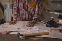 Mid section of craftswoman working with blueprints in workshop. — Stock Photo
