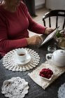 Mid section of senior woman using tablet in living room at home — Stock Photo