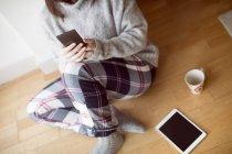 Gros plan de la femme utilisant un téléphone portable sur le sol à la maison . — Photo de stock