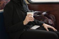 Средняя часть женщины в хиджабе пьет кофе во время поездки на поезде — стоковое фото