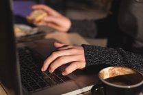 Sección media de la mujer que usa el ordenador portátil mientras toma café - foto de stock