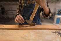 Mid section of craftswoman using hammer on wood in workshop. — Stock Photo