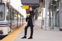 Woman in hijab using smartwatch at railway station — Stock Photo