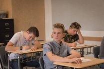 Thoughtful teenage boy sitting in classroom at university — Stock Photo