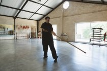 Combattant de kung fu pratiquant avec un long poteau dans un studio de fitness . — Photo de stock