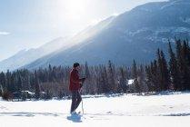 Homme qui marche avec des bâtons de ski dans le paysage enneigé durant l'hiver. — Photo de stock