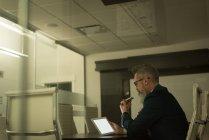 Lifschitz parler téléphone mobile tout en utilisant la tablette numérique de bureau — Photo de stock