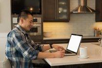 Hombre usando el ordenador portátil en la cocina en casa - foto de stock