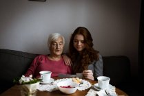 Grandmother and granddaughter looking at photograph in living room — Stock Photo