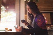 Mujer usando el teléfono móvil mientras toma café en la cafetería - foto de stock