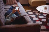 Женщина с мобильного телефона в гостиной на дому — стоковое фото