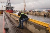 Trabajador portuario usando teléfono móvil en astillero - foto de stock