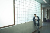 Male executive using mobile phone in office corridor — Stock Photo