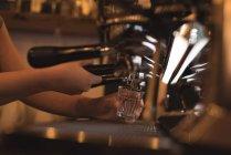 Бариста готовит кофе у стойки в кафе — стоковое фото