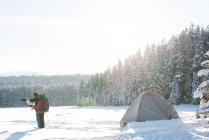 Pareja de turistas mirando el mapa en paisaje nevado durante el invierno - foto de stock