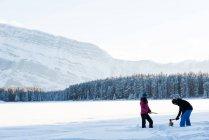 Пара різання дерева з сокирою в сніжний пейзаж у зимовий період. — стокове фото