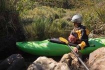 Жінка готується до каяках в річці при сонячному світлі. — стокове фото