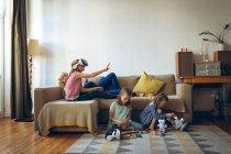 Mutter und Kindern beim Spielen im Wohnzimmer — Stockfoto
