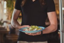 Mid section of waiter holding salad in cafe — Stock Photo