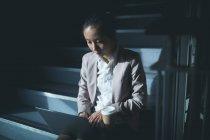 Женщины Исполнительный, с помощью ноутбука на лестнице в офис — стоковое фото