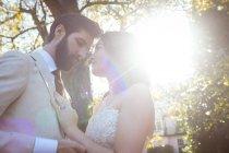 Romantisches Brautpaar an einem sonnigen Tag im Garten — Stockfoto