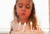 Little girl blowing out the candles on her birthday cake at home — Stock Photo