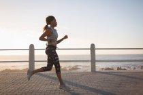 Молодая женщина бегает рядом с пляжем на закате — стоковое фото