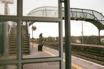 Жінка чекає поїзда з багажем на залізничні платформи — стокове фото