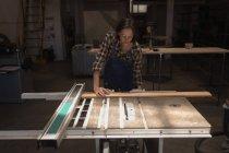 Junge Kunsthandwerkerin misst Holzstück in Werkstatt. — Stockfoto