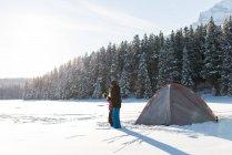 Intercambio de pareja caliente bebida juntos en paisaje nevado durante el invierno - foto de stock