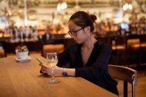 Femme à l'aide de téléphone portable tout en ayant le vin dans l'hôtel — Photo de stock
