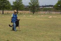 Mulher passeando com o cão de pastor no campo em um dia ensolarado — Fotografia de Stock